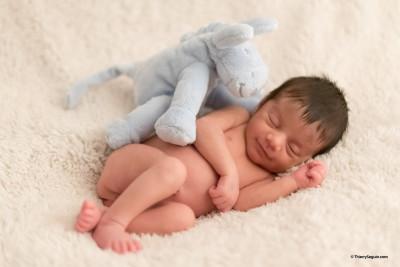 Nouveau-né souriant avec peluche Zaven