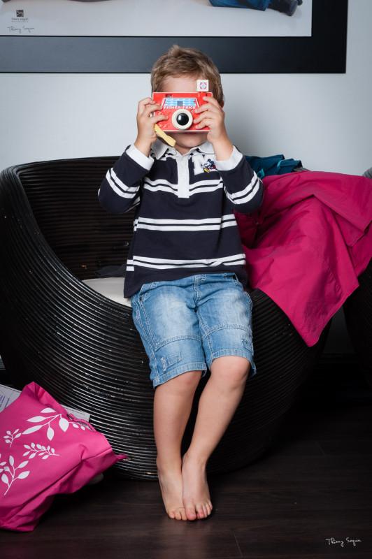 Enfant photographe derrière son appareil photo